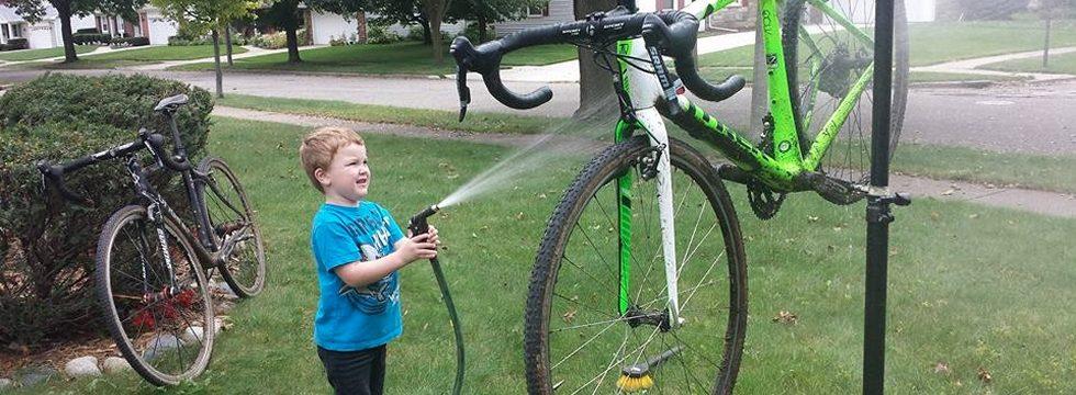 Boy washing bicycle